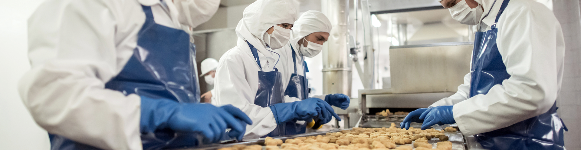 Workers in sanitary uniforms inspecting a conveyor belt of food at a food processing facility.