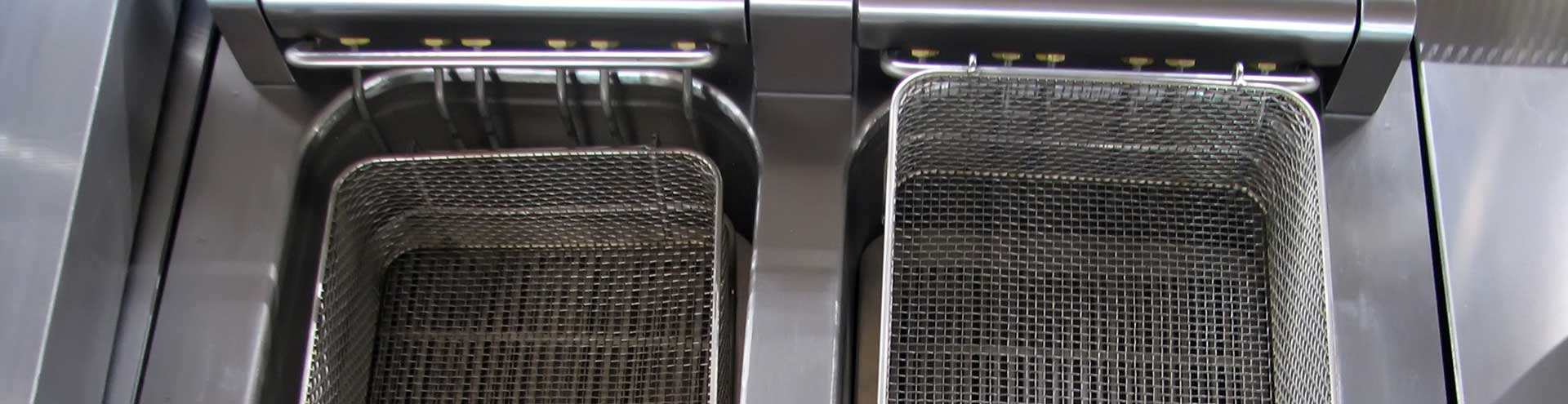 Two deep fryer baskets sitting on a stainless steel kitchen counter.